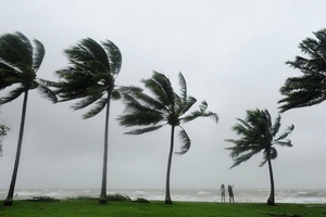 As high winds rip through Port Douglas a Coastguard volunteer, below, prepares for the cyclone. GETTY IMAGES