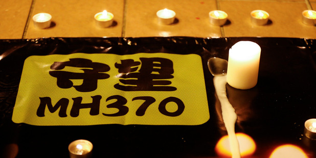 A banner is displayed during a candlelight vigil for passengers onboard the missing Malaysia Airlines Flight MH370. Photo / AP