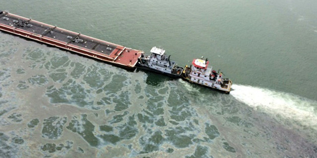 A barge loaded with marine fuel oil sits partially submerged in the Houston Ship Channel. Photo / AP