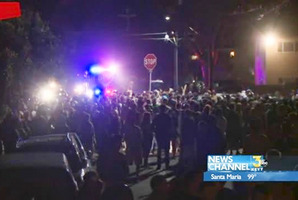 This video image provided by KEYT-TV shows a crowd confronting police during a weekend college party in Southern California that devolved into a street brawl. Photo / AP