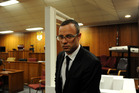 After a postponement was announced, Oscar Pistorius walks past the exhibited door, directly behind him, in court, through which he shot and killed Reeva Steenkamp. Photo / AP