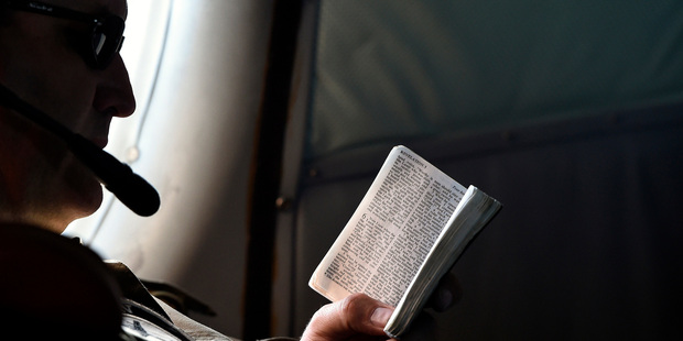 Flight Engineer Chris Poole reads a small bible aboard a Royal New Zealand Air Force (RNZAF) P-3 Orion on route to search over the southern Indian Ocean. Photo / AP