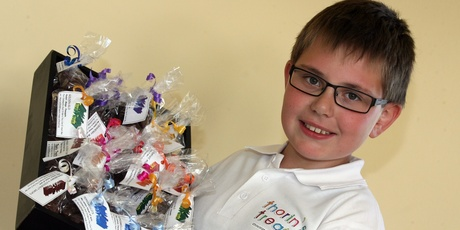 Thorin Williams, 11, with some of the chocolate treats he sells every week as he saves for his future security.