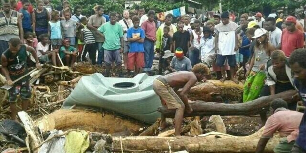 Solomon Islanders in Honiara recover what they can from the debris left by floodwaters.