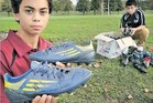 TREASURE: Michael Hoffman, 13, holds his most prized pair of boots, signed by Hurricanes stars Beauden Barrett and TJ Perenara, before putting them into the box with 15 other pairs the family's donating to the Hawke's BayToday Bring yer Boots campaign. At right is brother and rugby player Rocky, 14.