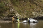 Rescue workers examine the car that crashed into the Waioeka River. Photo / Alan Gibson