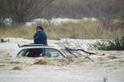 A  woman, left, waits to be rescued from her car roof after the flooded Kakanui River washed it off the road. Photo / Otago Daily Times