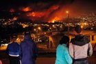 People watch as a forest fire rages towards urban areas in the city of Valparaiso, Chile.