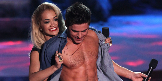 Rita Ora, left, rips open Zac Efron's shirt as he accepts the award for best shirtless performance on stage at the MTV Movie Awards. Photo / AP