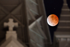 The moon glows a red hue during a lunar eclipse as it is framed between the steeples on the Annunciation Catholic Church in Houston. Photo / AP, Johnny Hanson
