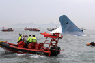 South Korean coast guard officers and rescue team members try to rescue passengers from the ferry Sewol. Photo / AP