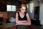 Amy Brosnahan in her bedroom, a tumble-down garage. Photo / Doug Sherring