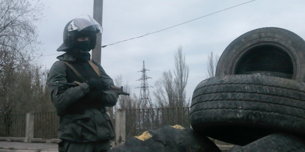 Armed pro-Russian activist stands at a makeshift checkpoint at the entrance into the eastern Ukrainian town of Slovyansk. Photo / AP