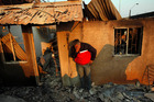 A man cries next to the remains of his house after a forest fire destroyed it in Valparaiso, Chile. Photo / AP