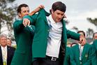 Defending champion Adam Scott helps Bubba Watson into his green jacket. Photo / AP