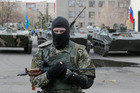 A masked gunman guards combat vehicles with Russian, Donetsk Republic and Ukrainian paratroopers, flags and gunmen on top. Photo / AP