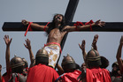 A Filipino devotee that is nailed to a cross reacts as actors dressed as Roman soldiers lift him as they re-enact the crucifixion of Jesus Christ. Photo / AP