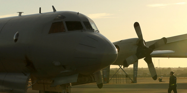 A flight crewman from a Royal Australian Air Force P-3 Orion walks towards the aircraft at RAAF Base Pearce. Photo / AP