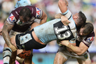 Chris Heighington of the Sharks is lifted into a heavy tackle by Anthony Watmough and Brenton Lawrence of the Sea Eagles. Photo / Getty Images.
