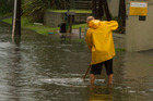 A resident clears the drains on Oceanbeach Rd. Photo/Sharp Focus Photography