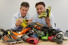 Sports reporter Shane Hurndell (left) and chief reporter Greg Taipari pictured with boots donated by the public for the Bring yer Boots campaign. Photo/Glenn Taylor