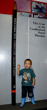A child stands next to a<BR>very tall pencil at the<BR>museum in Keswick.