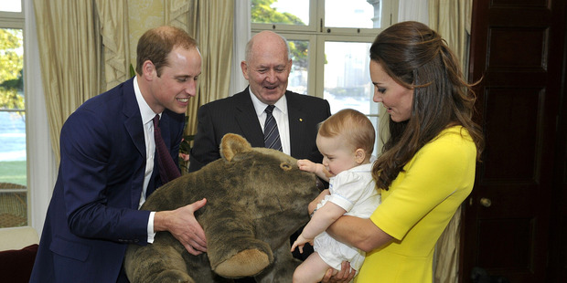 Prince George of Cambridge, with his parents Prince William, Duke of Cambridge and Catherine, Duchess of Cambridge, receives a gift at Admiralty House in Sydney, Australia. Photo / Getty Images