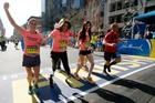 Double amputee Celeste Corcoran (centre), a victim of last year's bombings, crosses the finish line with her sister Carmen Acabbo (left) and daughter Sydney, who was also wounded last year. Photo / AP