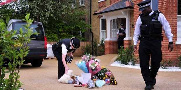 Police officers adjust tributes left outside the house in New Malden, south London. Photo / AFP