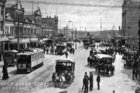 A 1907 traffic medley of electric trams, horse drawn buses and a solitary motor car (parked beside the righthand curb) share Lower Queen St together. File photo / NZ Herald Archive
