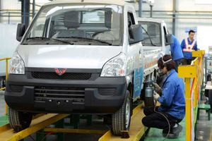 Workers put the finishing touch to a pickup at a factory of SGMW, a joint venture between Chinese carmakers and General Motors in Qingdao in east China's pic/AP