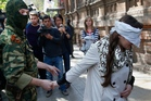 A masked pro-Russian man escorts pro-Ukrainian activist and journalist Irma Krat in Slovyansk, eastern Ukraine. Photo / AP