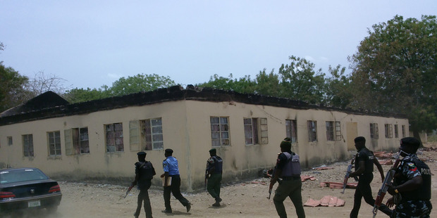 Security walk past burned government secondary school Chibok, where gunmen abducted more than 200 students in Chibok, Nigeria. Photo / AP