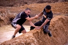 Steve Deane needs the help of Pua Magasiva on the Tough Mudder course at Hampton Downs. Photo / Dean Purcell