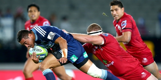 Blues halfback Bryn Hall attempts to break the tackle of Reds prop James Slipper last night. Hall had a strong game. Photo / Getty Images