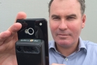 Glenn Milnes of ikeGPS with the firm's new Spike device, which attaches to a smartphone