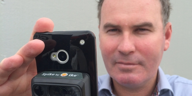 ikeGPS managing director Glenn Milnes with the firm's new Spike device, which attaches to a smartphone.