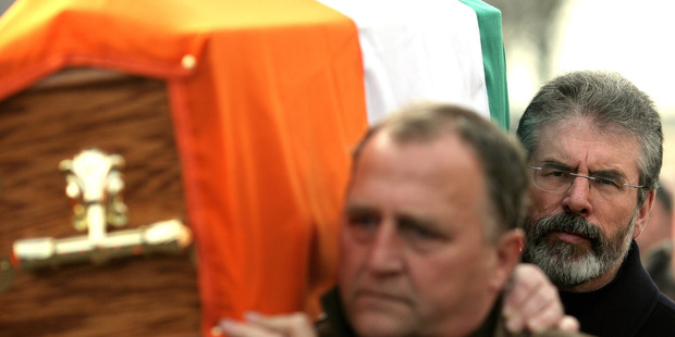 2008 file photo of Sinn Fein President Gerry Adams, right, carrying the coffin of senior IRA commander Brendan Hughes, in west Belfast. Photo / AP