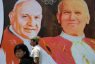 Two people walk in front of pictures of Pope John XXIII, left, and Pope John Paul II in Guatemala City. Photo / AP