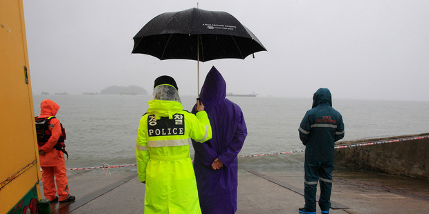 A police officer holds up an umbrella for a relative of a passenger aboard the sunken ferry Sewol. Photo / AP