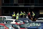 Police stand outside Corpus Christi Catholic College. Photo / AP