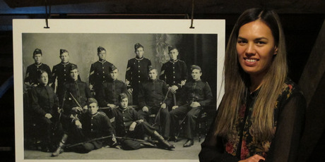 Kerikeri Mission Station visitor services coordinator Katrina Matete with a portrait of Ernest Kemp and other military cadets at Wanganui Collegiate. PHOTO / PETER DE GRAAF