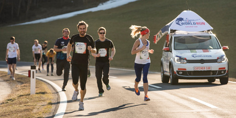 Participants run in front of the Wings for Life World Run Catcher Car in Oberwolz, Austria on March 13th, 2014 // Samo Vidic/Red Bull