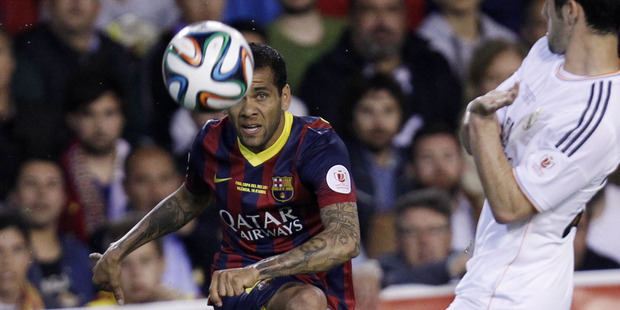 Dani Alves picked up and banana thrown by an opposition fan and eat it before taking a corner. Photo / AP
