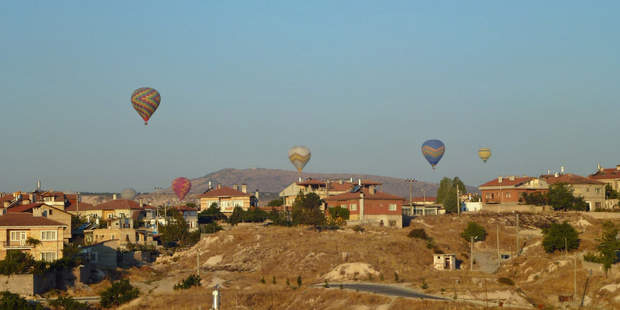 Brightly-coloured balloons, some flying low, in the sky over Cappadocia. Photo / Justine Tyerman