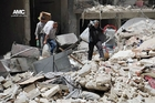 People in Aleppo salvage their belongings after a bombing attack. Photo / AP