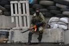 A masked and armed pro-Russian militant guards barricades near Slovyansk. Photo / AP