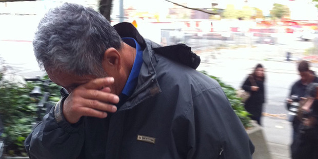 Cunbin Zhang hides his face as he heads into the Christchurch District Court today. Photo / APNZ
