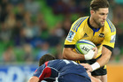 Cory Jane of the Hurricanes is tackled by Tom English of the Rebels. Photo / Getty Images
