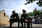 Pro-Russian Cossacks pause to eat outside the regional administration building in Donetsk, Eastern Ukraine yesterday. Photo / AP